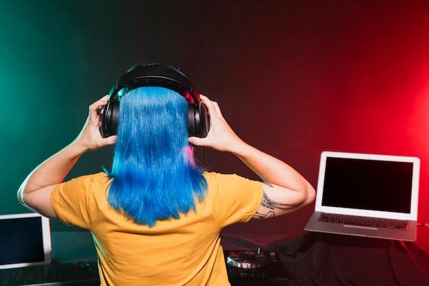 Vista posterior dj femenina mezcla en el club