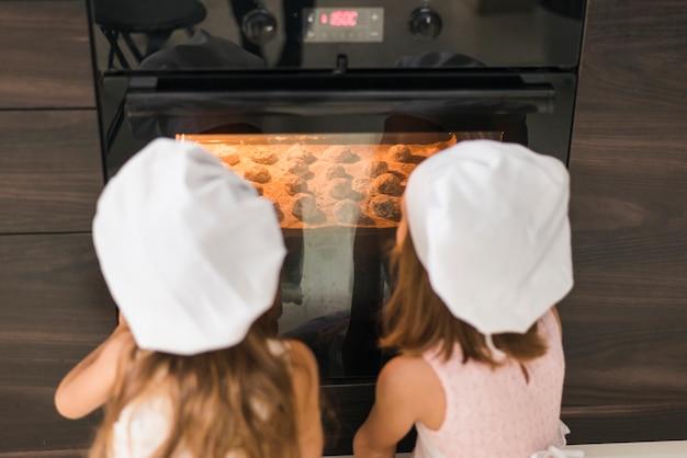 Vista posterior de dos hermanas en gorro de cocinero mirando bandeja de galletas en horno