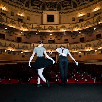 Vista posterior de dos intérpretes inclinándose en el escenario