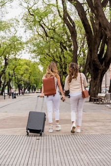 Vista posterior de dos mujeres jóvenes caminando en el parque con bolsa de equipaje