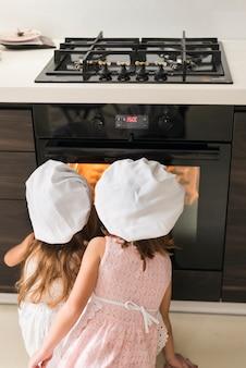 Vista posterior de dos niños con gorro de cocinero mirando bandeja de galletas en horno