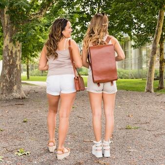 Vista posterior de dos turistas mujeres con su bolsa de cuero de pie en el parque