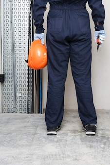 Vista posterior de electricista con casco de sujeción y alicates