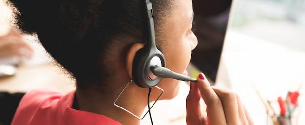 Vista posterior de la empresaria afro usando auriculares con micrófono en el trabajo