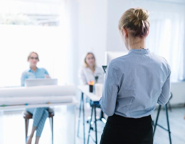 Vista posterior de una empresaria dando presentación en la reunión.