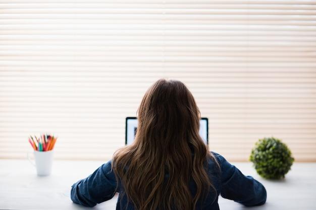 Vista posterior de empresaria hipster usando laptop en su escritorio