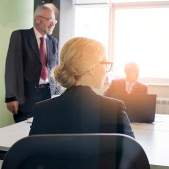 Vista posterior de la empresaria joven rubia con su colega en la oficina