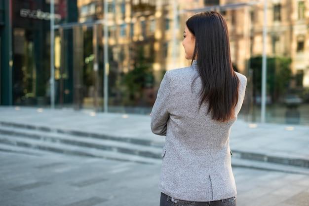 Vista posterior de la empresaria posando al aire libre con los brazos cruzados.