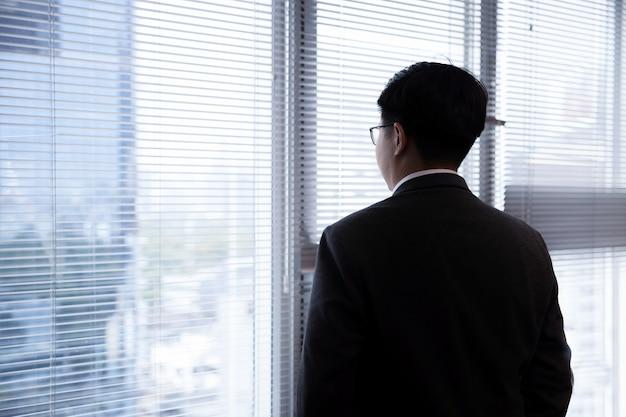 Vista posterior del empresario asiático en un traje mirando a través de la ventana de office con copyspace en blanco