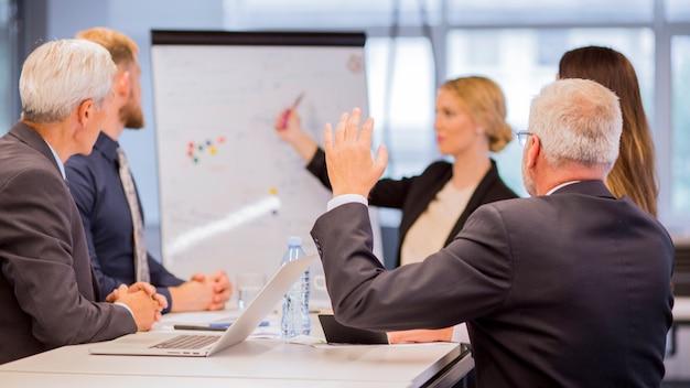 Vista posterior del empresario senior haciendo preguntas durante la presentación
