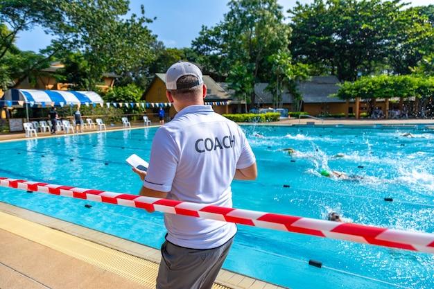 Vista posterior de un entrenador masculino en camisa blanca de entrenador mirando a sus nadadores compitiendo