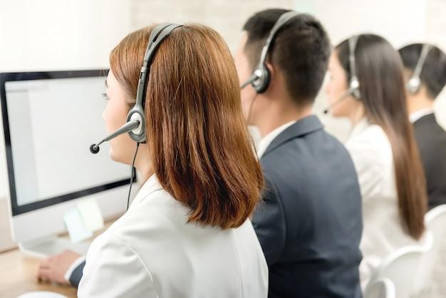 Vista posterior del equipo de agente de servicio al cliente de telemarketing asiático