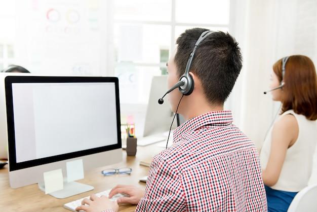 Vista posterior del equipo de agente de servicio al cliente de telemarketing que trabaja en call center