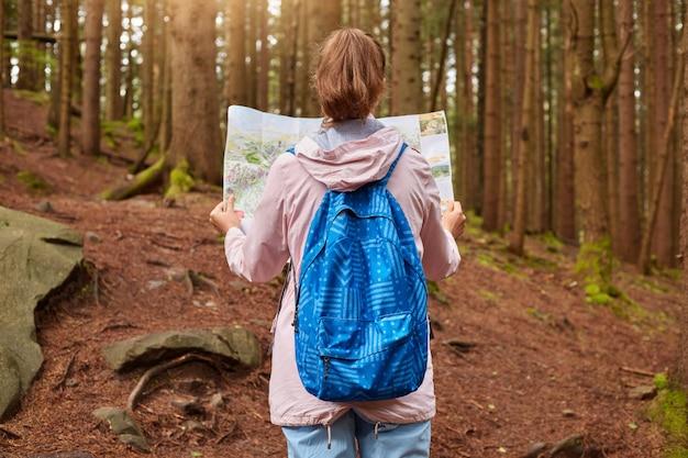 Vista posterior del esbelto viajero con cola de caballo con jeans, mochila azul, chaqueta rosa, mirando el mapa, tratando de no perderse
