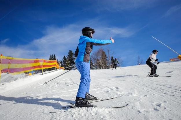Vista posterior del esquiador femenino en un día soleado en la estación de esquí en una pista de esquí dando el pulgar hacia arriba