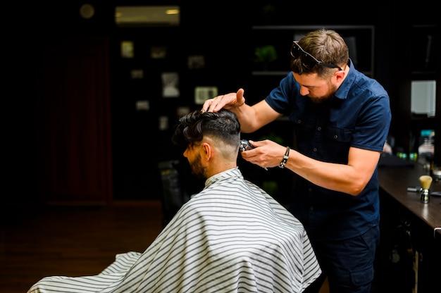 Vista posterior del estilista cortando el cabello del cliente