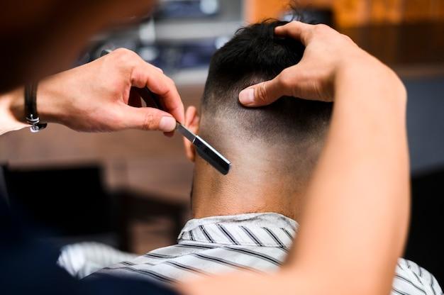 Vista posterior del estilista que afeita el cabello del cliente