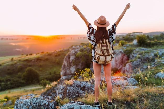 Vista posterior de un excursionista femenino con el brazo levantado