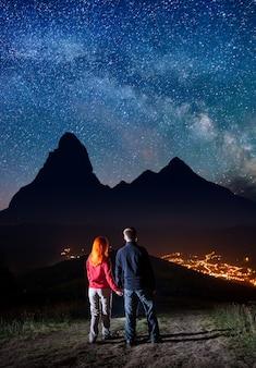 Vista posterior de los excursionistas de pareja tomados de las manos, de pie sobre una colina