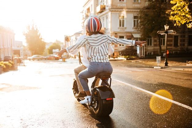 Vista posterior de la feliz pareja africana monta en moto moderna en la calle