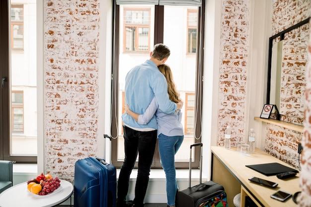 Vista posterior de la feliz pareja amorosa en la habitación del hotel, abrazándose y de pie en la ventana