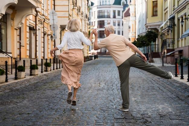 Vista posterior de la feliz pareja de ancianos en la ciudad