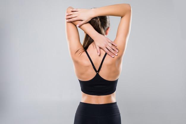 Vista posterior foto de una mujer joven sana en ropa deportiva aislado en la pared blanca