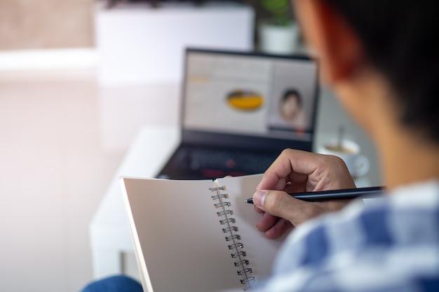 La vista posterior de la gente de negocios hablando a través de una conferencia web.