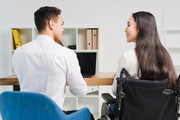Vista posterior de una gente de negocios joven sonriente mirando el uno al otro en el lugar de trabajo