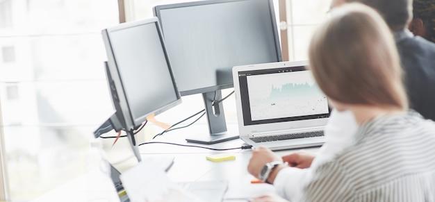 Vista posterior de la gente que trabaja en la oficina con las computadoras portátiles