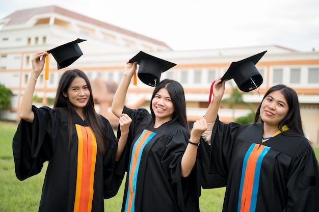La vista posterior de los graduados que usan batas negras para prepararse para los títulos universitarios.