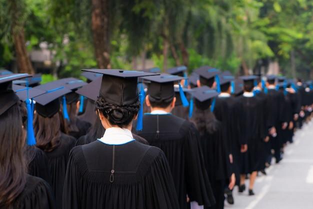 La vista posterior del grupo de graduados universitarios en vestidos negros se alinea para obtener el título en la ceremonia de graduación universitaria. felicitación de educación de concepto, estudiante, exitoso para estudiar.