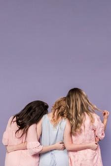 Vista posterior del grupo de mujeres abrazados con espacio de copia