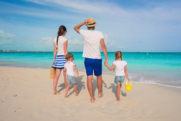 Vista posterior de hermosa familia con dos niños en playa tropical