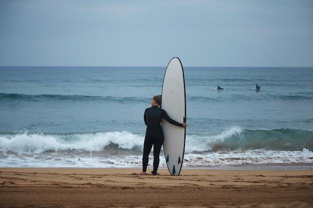 Vista posterior de la hermosa joven surfista abrazando su longboard en la orilla del océano y mirando las olas antes de surfear