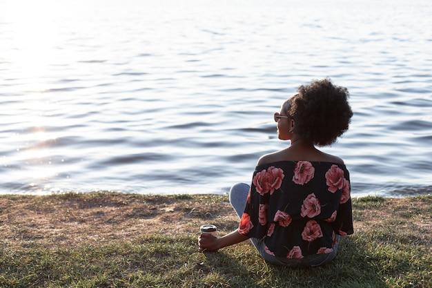 Vista posterior hermosa mujer africana sentada en el suelo