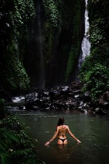 Vista posterior de hermosa mujer bañándose y relajándose en la piscina natural antes de la cascada en el parque natural en la isla tropical. hermosa cascada en bali, indinesia