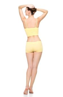 Vista posterior de un hermoso cuerpo femenino deportivo en ropa interior amarilla posando aislada en la pared blanca