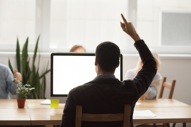 Vista posterior en el hombre africano que levanta la mano que celebra la victoria en línea que mira la pantalla de computadora