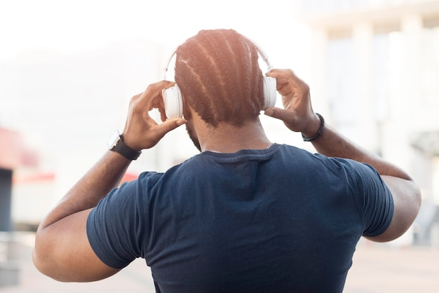 Vista posterior del hombre afroamericano escuchando música a través de auriculares
