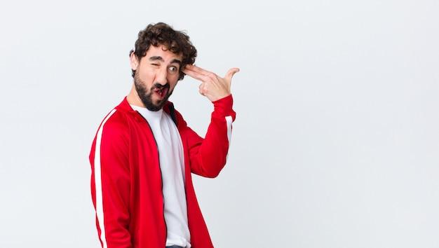 Vista posterior del hombre barbudo joven que parece infeliz y estresado, gesto de suicidio haciendo signo de arma con la mano, apuntando a la cabeza contra la pared del espacio de copia