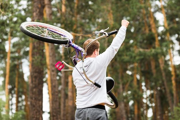 Vista posterior hombre con bicicleta en el hombro