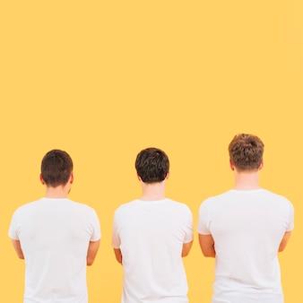 Vista posterior de un hombre en camiseta blanca de pie contra el fondo amarillo