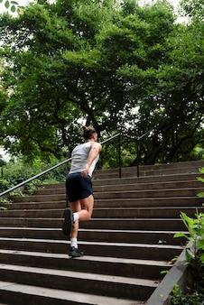 Vista posterior del hombre corriendo escaleras arriba