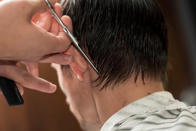 Vista posterior de un hombre cortándose el pelo