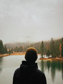 Vista posterior de un hombre en un entorno natural.