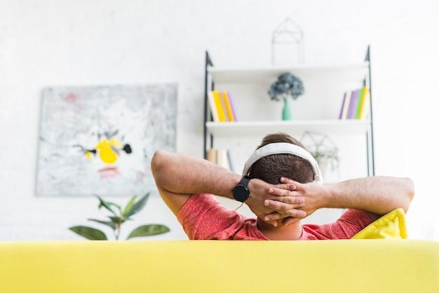 Vista posterior de un hombre escuchando música en auriculares