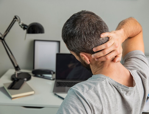 Vista posterior del hombre estirando mientras trabaja desde casa