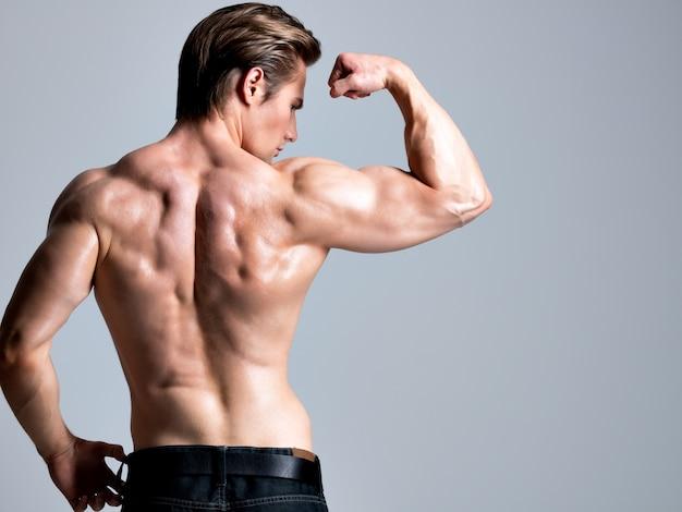 Vista posterior de hombre guapo con sexy cuerpo hermoso musculoso posando.