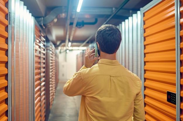 Vista posterior del hombre hablando por teléfono inteligente